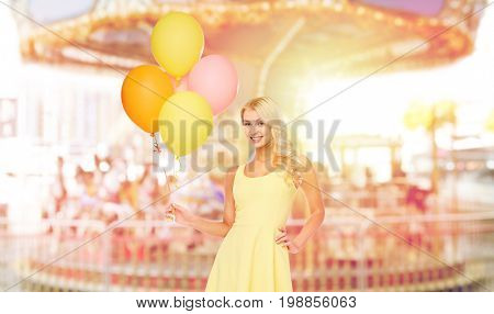 people, entertainment and summer concept - happy young woman or teen girl in yellow dress with helium air balloons over carousel background