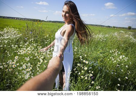 Follow me, Beautiful sexy young brunette woman holds the hand of a man in flowers field