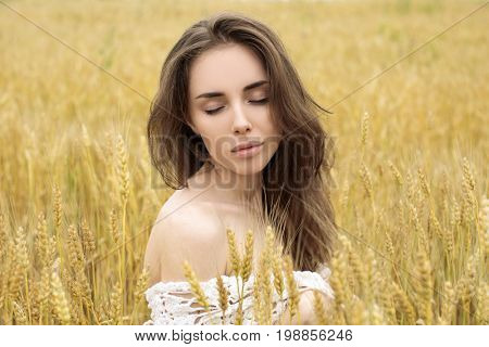 Portrait of a young girl on a background of golden wheat field, summer outdoors