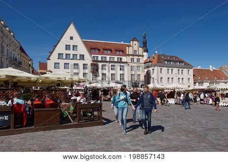 TALLINN, ESTONIA - JUNE 10, 2017: People resting on the Town Hall square. The Old Town is one of the best preserved medieval cities in Europe and is listed as a UNESCO World Heritage Site