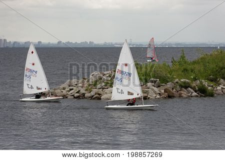 ST. PETERSBURG, RUSSIA - JULY 5, 2017: Training in sailing on Laser 4.7 dinghy in the Gulf of Finland near the yacht club of St. Petersburg. Yacht club organizes sailing classes for all ages