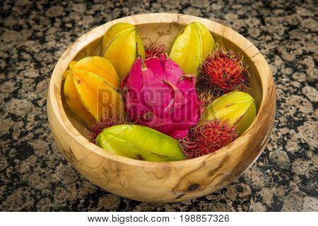 Fruit bowl with exotic star fruit dragon fruit and rambutan colorful natural organic sweet food in wood bowl on granite counter