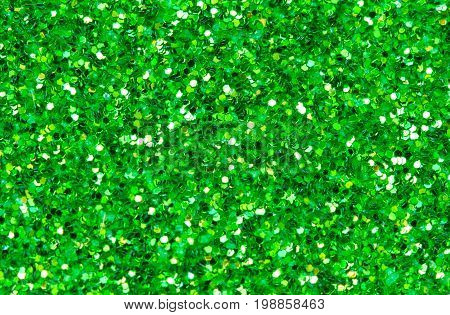 Green abstract background. Green glitter closeup photo. Green shimmer wrapping paper. Sparkling glitter festive backgrop. Christmas or New Year template. Glitter texture macrophoto. Shiny green card