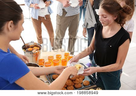Volunteer sharing food with poor woman. Poverty concept