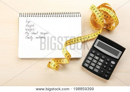 Diet concept. Measuring tape, calculator and notebook on wooden background