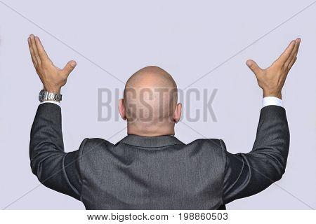 Rear view from a desperate bald head businessman praying looking upward.
