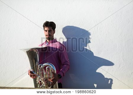Musician with Tuba instrument near the white wall the shadow of the tool.