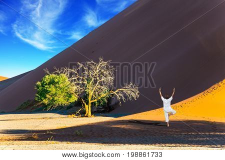 The concept of extreme and exotic tourism. Purple and yellow dune of the Namib desert. An elderly woman practicing yoga in the desert