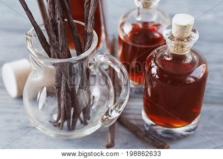 Bottles with aromatic extract and dry vanilla beans in jug on table