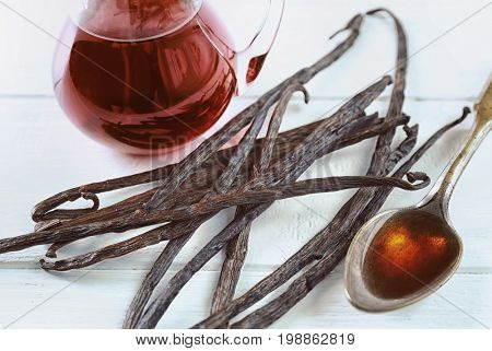 Dry vanilla beans and spoon with aromatic extract on table