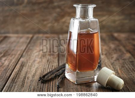 Bottle with aromatic extract and vanilla beans on table