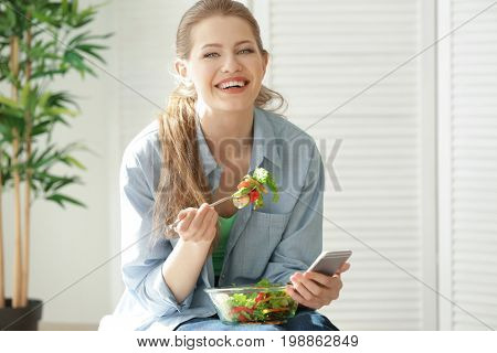 Young woman using mobile phone for counting calories while eating salad. Weight loss concept