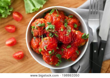 Bowl with delicious turkey meatballs and tomato sauce on wooden table