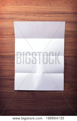 Blank paper with four fold mark on wooden table.Excellent for overlaying letters and documents. Intentionally shot in low key muted tone.