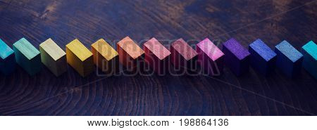 Colored wooden blocks diagonally aligned on old vintage wooden table. For something with concept of variations or diversity. Intentionally shot in muted tone and low key.