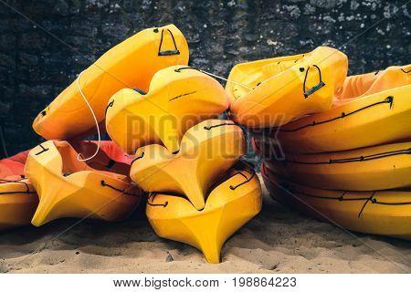 Stacked orange kayaks on a beach