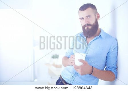 Young businessmen holding a tea cup standing in office