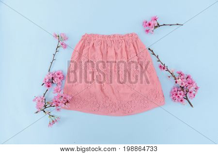 pink skirt and flowering cherry, on blue background .