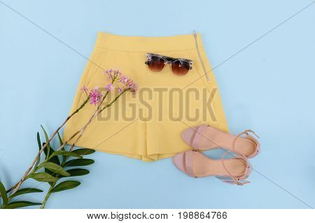 Summer yellow shorts ,sunglasses and lilac flowers on blue background .