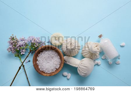 lilac flowers ,salt in bowl , candle,soap with herbal ball , on blue background