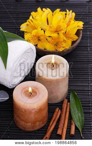 Spa setting on mat with yellow orchid in bowl ,candle, towel,leaf