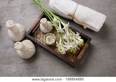 Spa setting with a lilac flowers and ball, salt in bowl, in basket on gray background