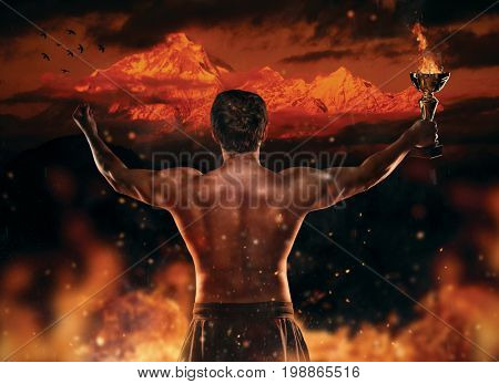 Muscular man holding burning trophy cup, looking at high mountain peak. Concept of success, hard work and conquest of the target. High resolution image