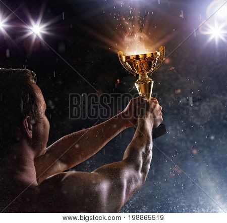 Back view of man fighter holding trophy cup in hands, victory gesture. Concept of hard work, glory and success. Very high resolution image