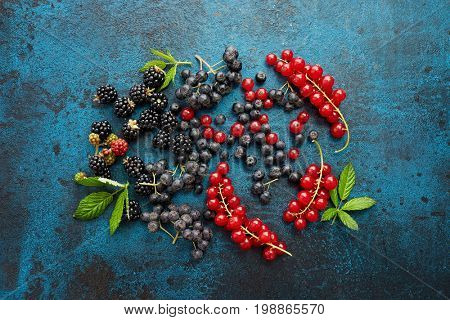 Assorted fresh berries with leaves on metal background. Mix of fresh berries with leaves on textured metal background.
