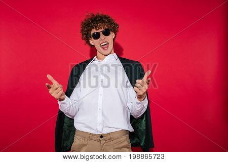 Happy excited man in white shirt and jacket pointing two fingers at camera isolated over red background