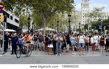 BARCELONA, SPAIN - SEPTEMBER 30, 2016: People waiting to cross a crosswalk at the end of Rambla de Catalunya facing La Rambla in Barcelona, Spain. This is one of the busiest crosswalks in the city
