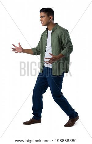 Frustrated man gesturing against white background