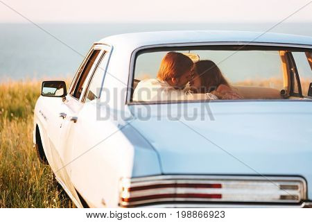 Back view of a smiling attractive couple in love sitting and kissing on a back seat of a car