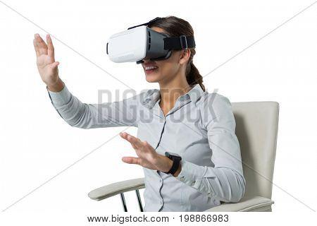 Female executive using virtual reality headset against white background
