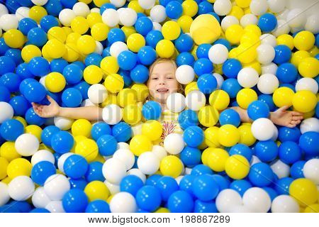 Happy Little Girl Having Fun In Ball Pit In Kids Indoor Play Center. Child Playing With Colorful Bal