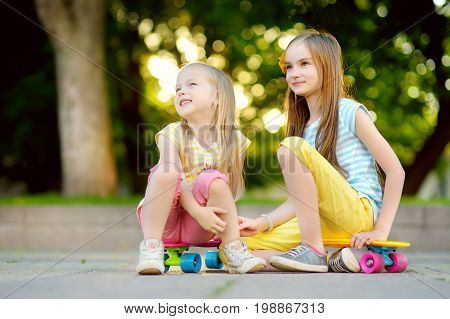 Two Pretty Little Girls Learning To Skateboard On Beautiful Summer Day In A Park. Children Enjoying