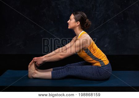 Woman doing Hatha yoga Ashtanga Vinyasa yoga asana Paschimottanasana - seated forward bend beginner variation on dark grunge background