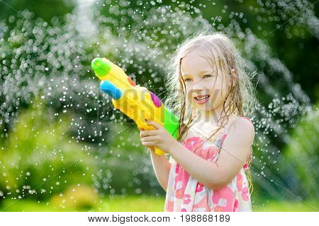 Adorable Little Girl Playing With Water Gun On Hot Summer Day. Cute Child Having Fun With Water Outd