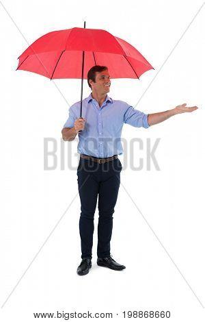 Smiling male executive holding umbrella against white background