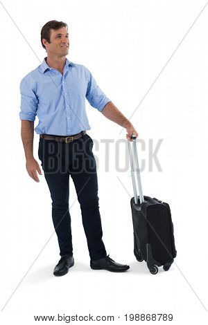 Smiling male executive with luggage against white background