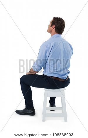 Male executive sitting on stool against white background