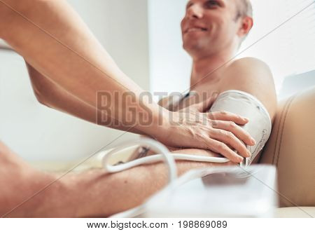 A nurse fastens the pulsometr cuffs on the patient's arm