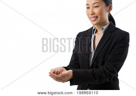 Smiling businesswoman with hand cupped against white background