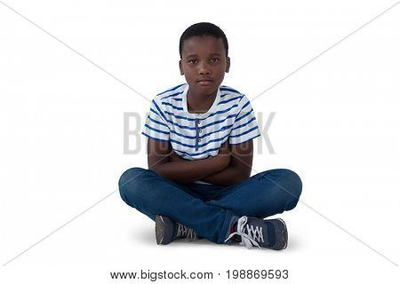 Portrait of sad boy sitting on floor against white background