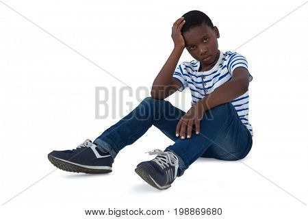 Portrait of sad boy sitting with hand on head against white background
