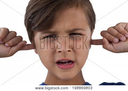 Portrait of cute boy covering his ears against white background