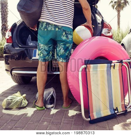 closeup of a young caucasian man putting in or taking out beach stuff from the trunk of his car, such as a beach chair, a pink swim ring or a inflatable beach ball