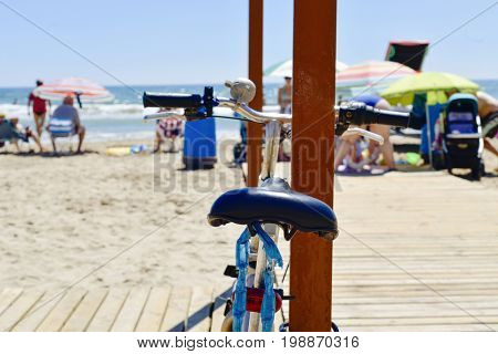 closeup of a bicycle parked a the seafront of a beach with unrecognizable people in the background