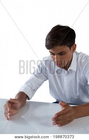 Teenage boy pretending to work on an invisible object against white background