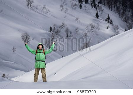 Man with backpack standing on snowy mountain slope. Alpinist or mountain hiker.